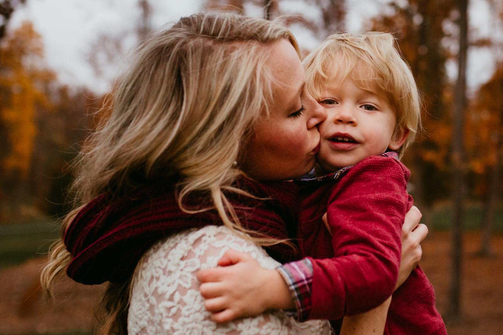 Mom kissing toddler son at The Barn at One Loudoun, Ashburn, Virginia in the fall