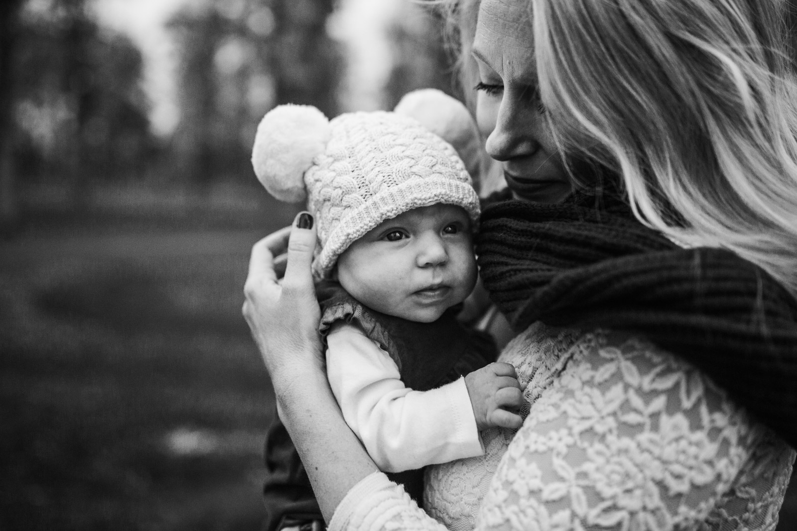 Black and white; mom holding infant daughter in knit hat at The Barn at One Loudoun, Ashburn, Virginia