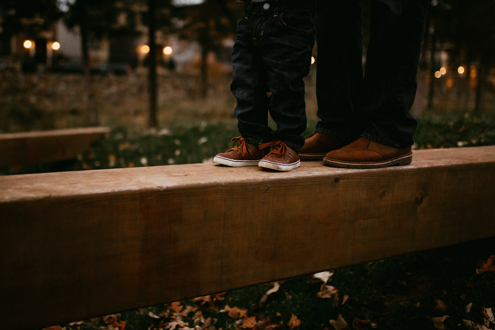 Close up of brown shoes as dad helps son across a wooden beam at The Barn at One Loudoun, Ashburn, Virginia