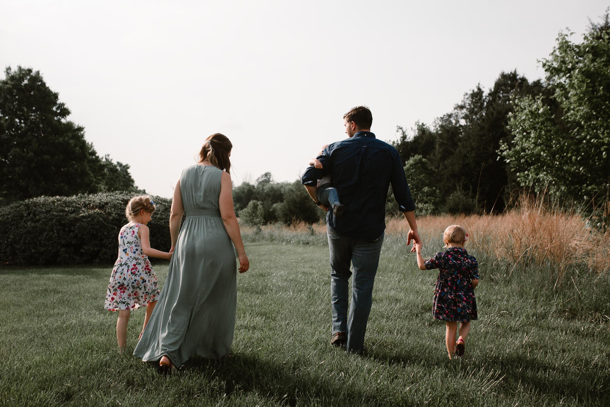 Family holding hands and walking through a field at Beaverdam Run in Ashburn, Virginia