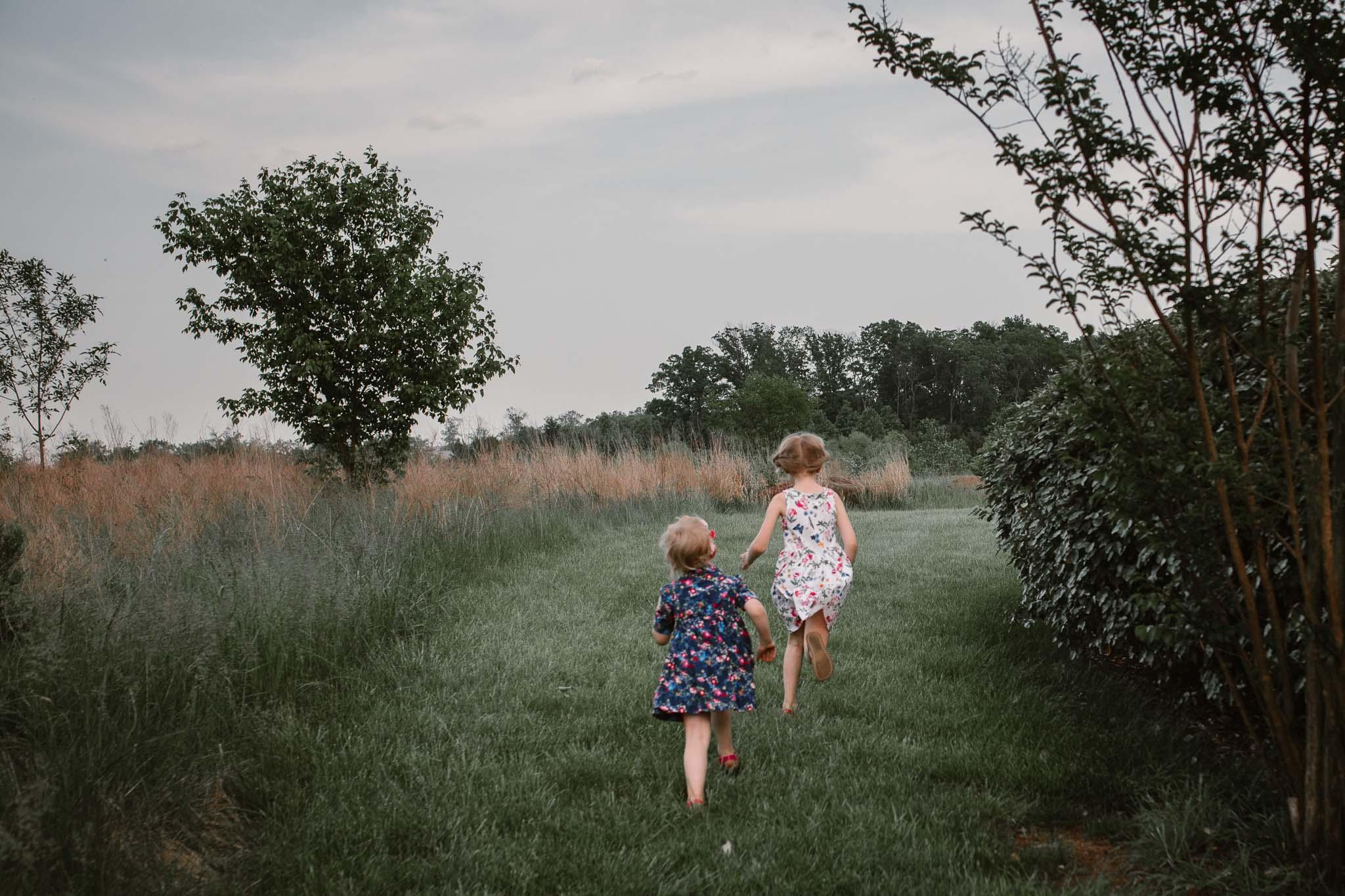 Two sisters race away through a field  at Beaverdam Run in Ashburn, Virginia