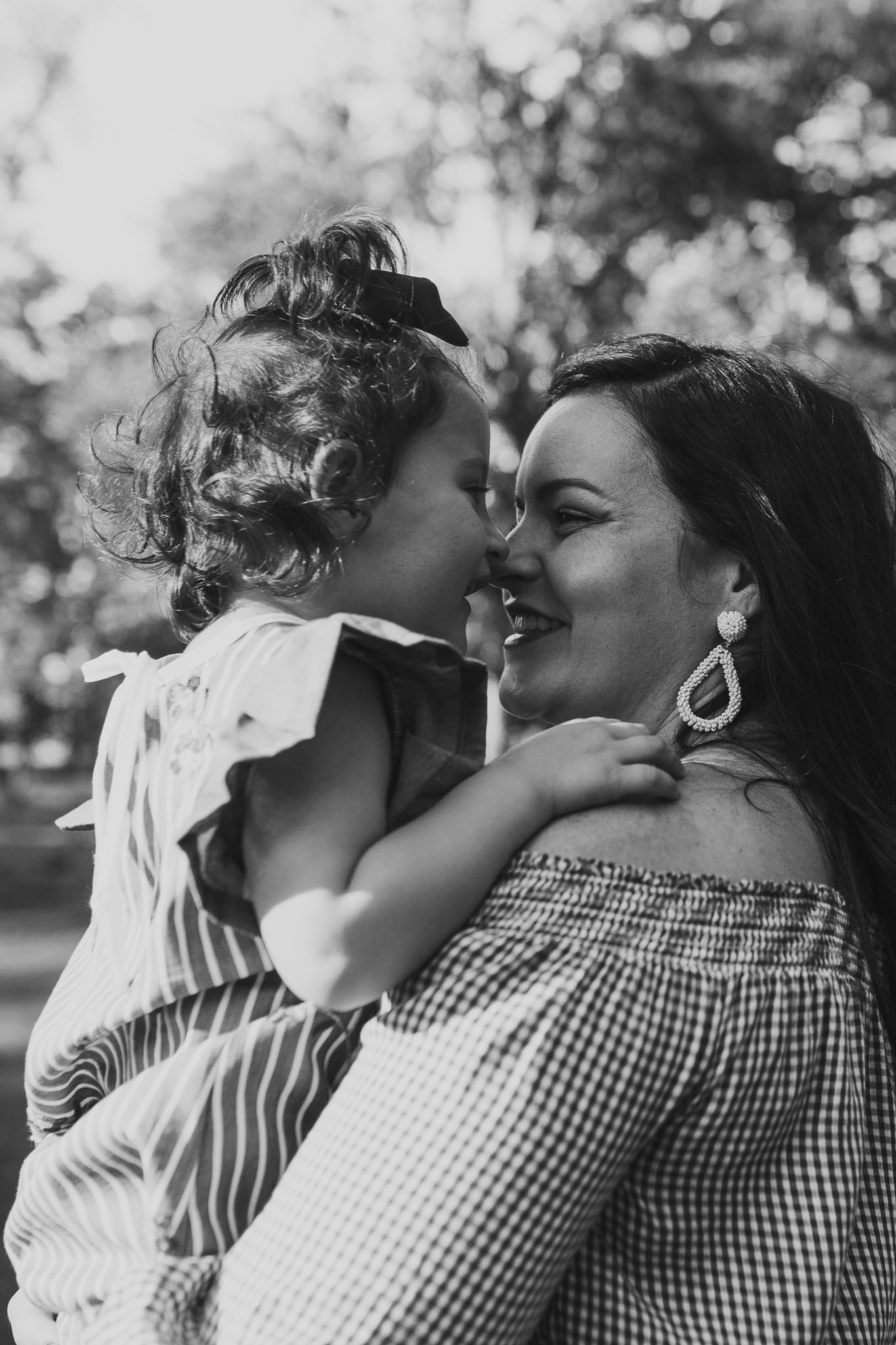 Black and white mother and daughter smile and kiss at The Barn at One Loudoun in Ashburn, Virginia