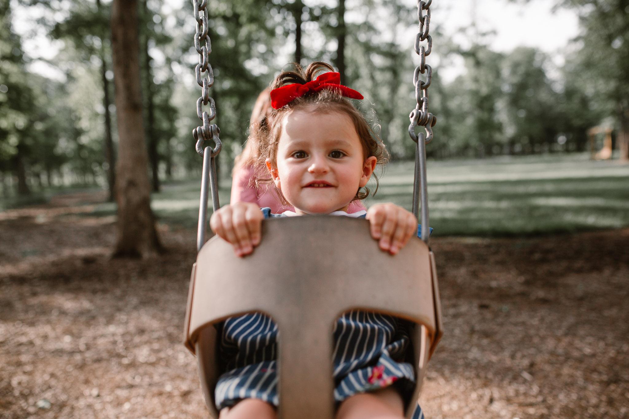 Toddler swinging at The Barn at One Loudoun in Ashburn, Virginia