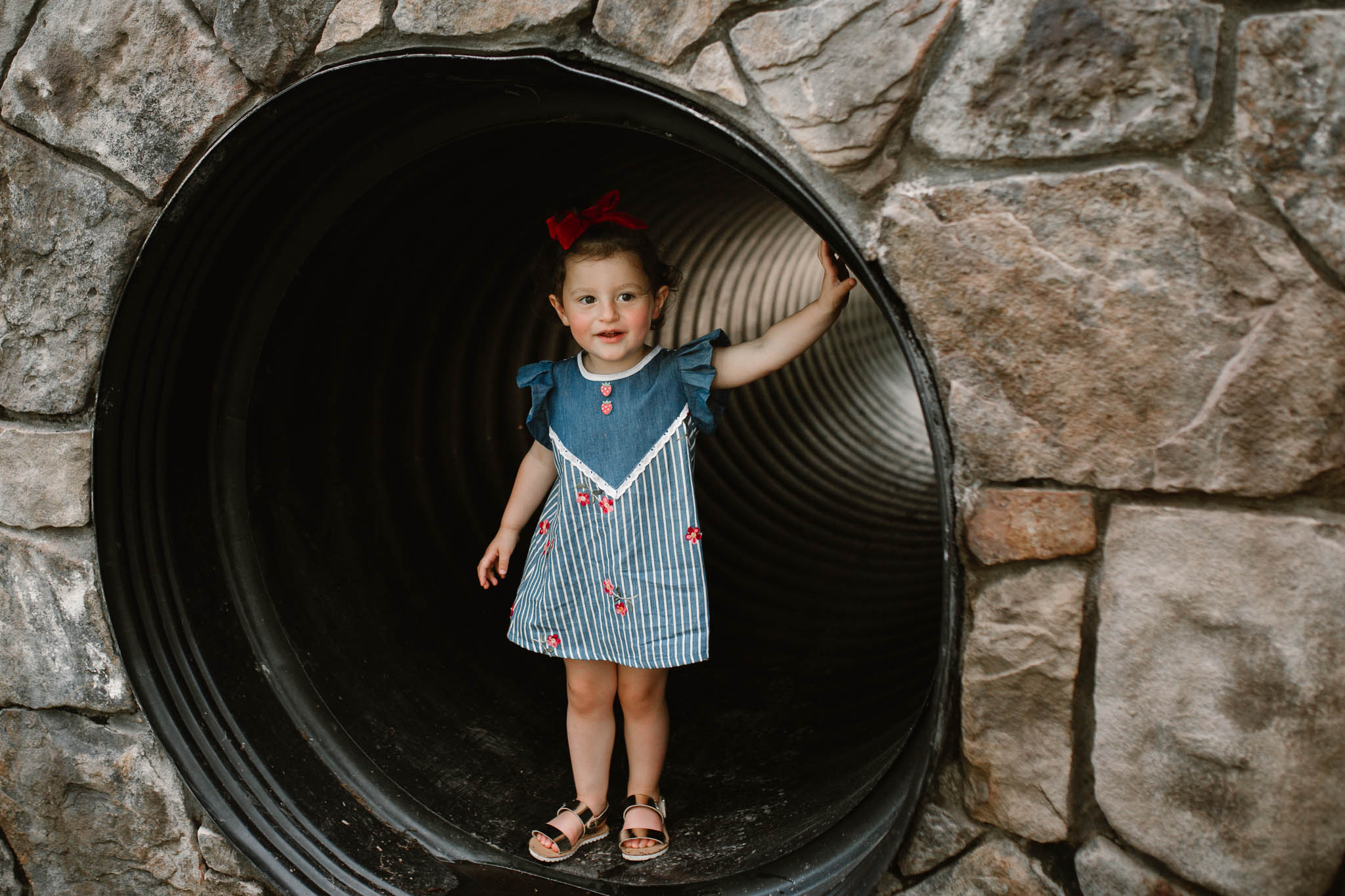 Little girl in a blue dress stands at the edge of a tunnelat The Barn at One Loudoun in Ashburn, Virginia