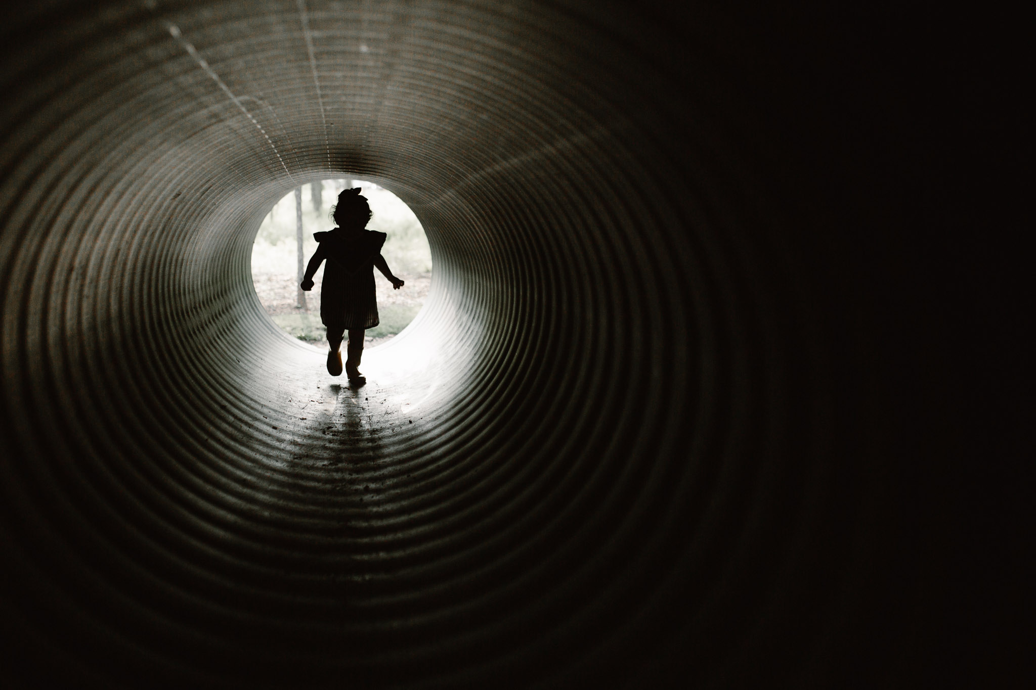 silhouette of a little girl running through a tunnel at The Barn at One Loudoun in Ashburn, Virginia