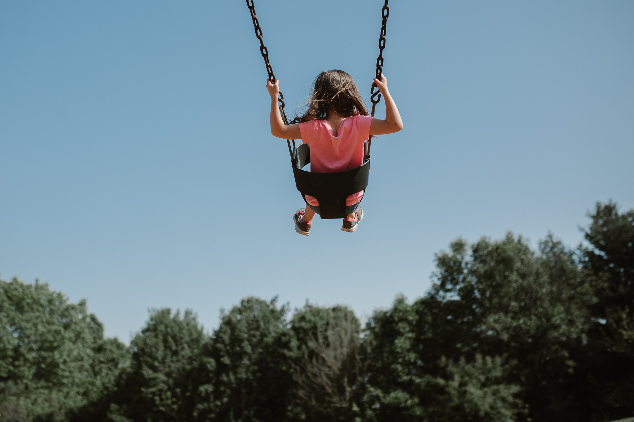 Girl in a pink shirt swinging high on a clear blue day documentary photography ashburn Virginia