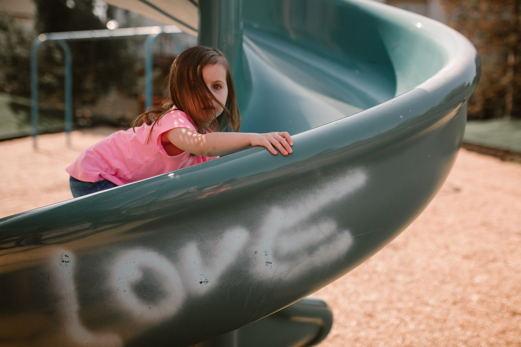 Toddler climbs up a  green slide with Love graffiti painted on documentary lifestyle photography ashburn virginia