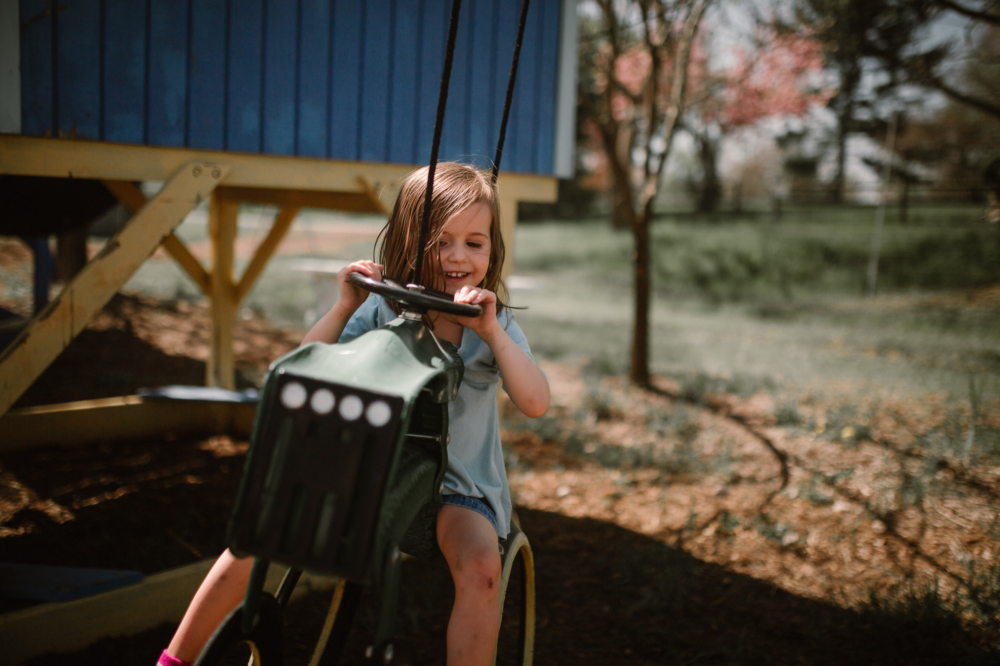girl in a blue dress rides a swing shaped like a tractor at Burnside Farm in Virginia