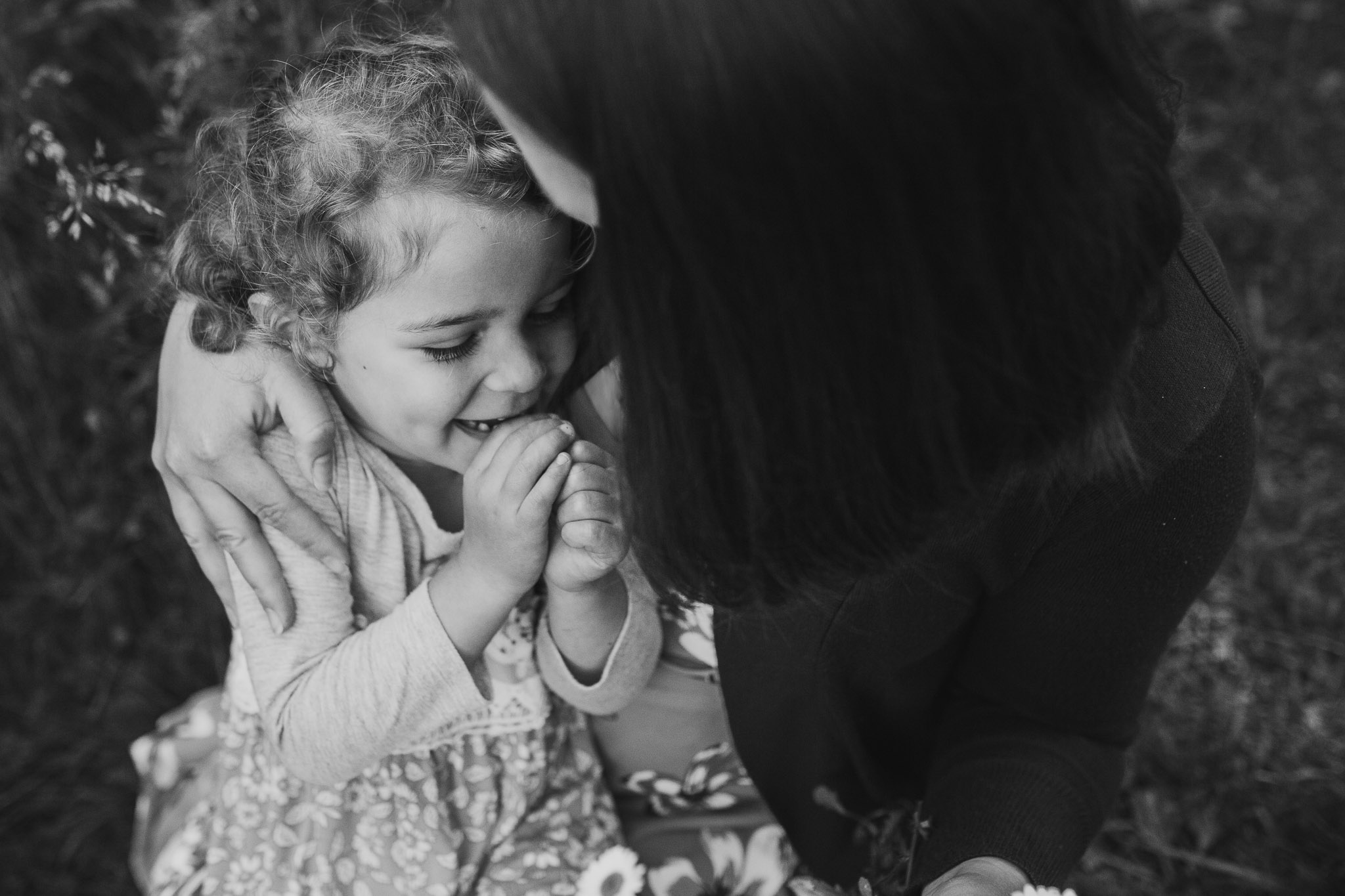 lifestyle family photography black and white mother and daughter hug and laugh at Bles Park in Ashburn, Virginia