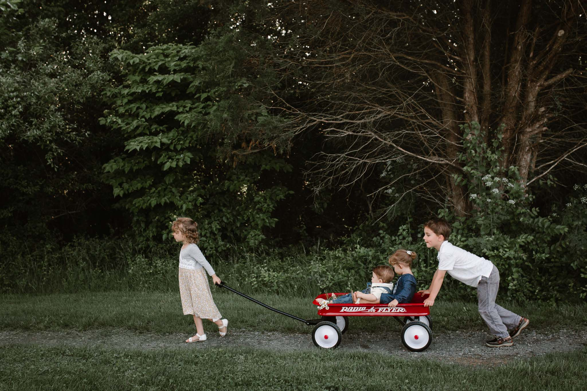 Lifestyle family photography four siblings riding in and pushing a red radio flyer wagon  at Bles Park in Ashburn, Virginia
