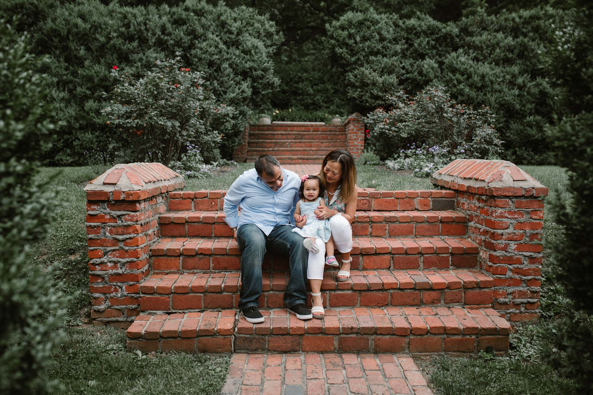 Family of three sits on brick steps at Morven Park in Leesburg, Virginia