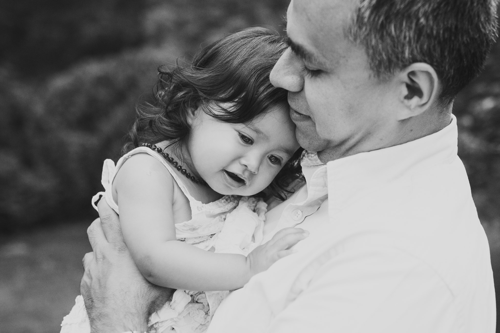 black and white; little girl hugging her dad and leaning her headon his chest at Morven Park in Leesburg, Virginia
