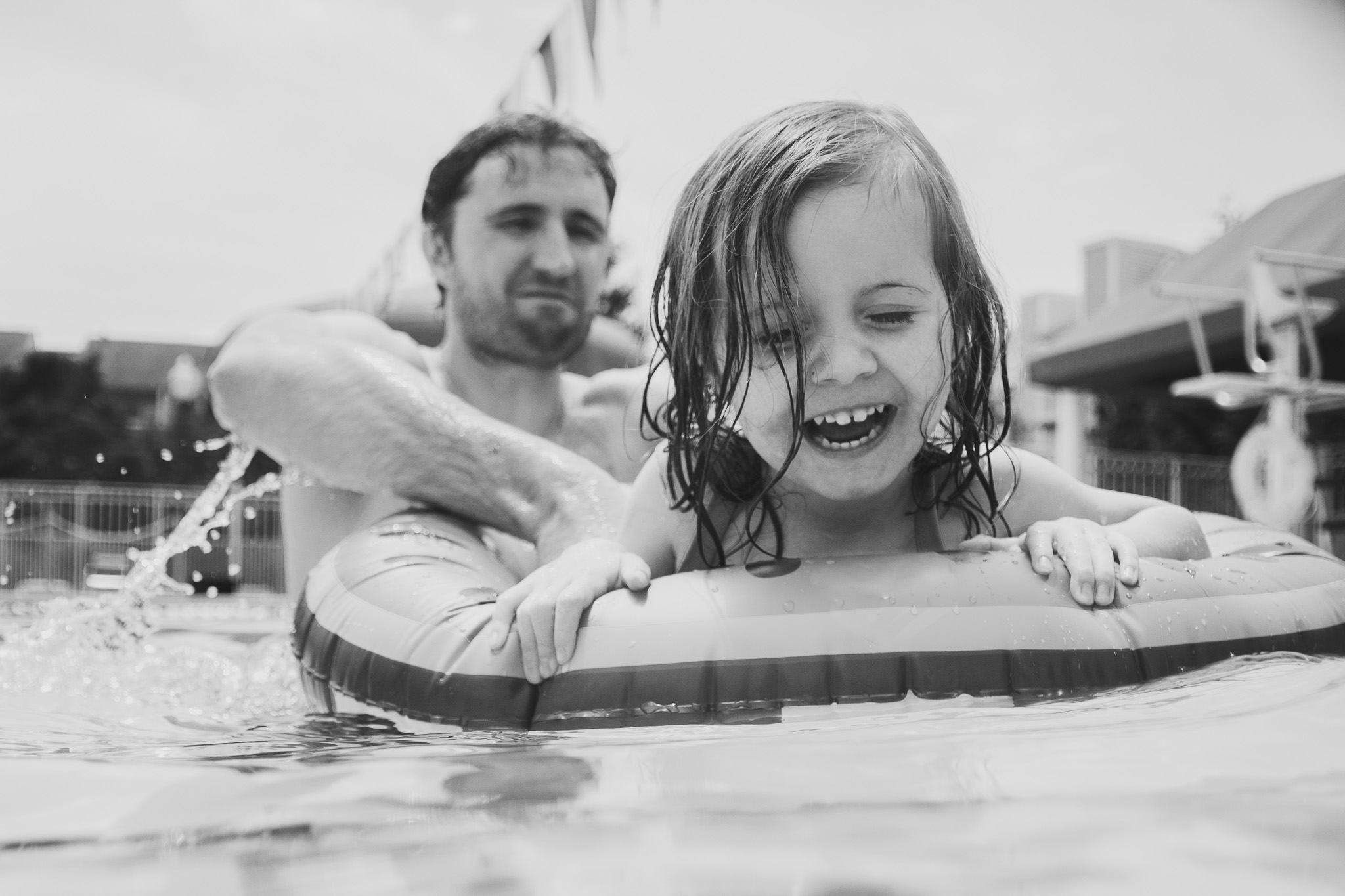 Black and white; dad twirls his daughter sitting in an inner tube in the pool