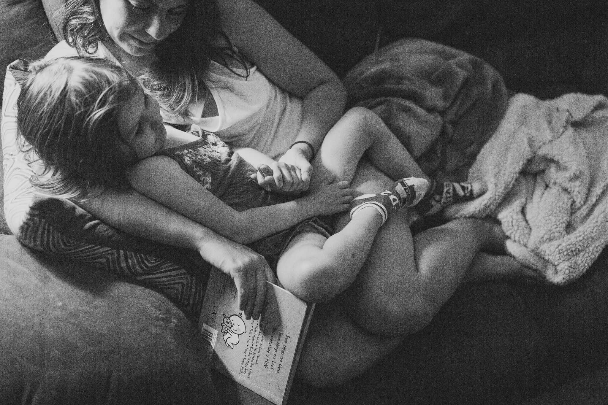 black and white; mother and daughter cuddle together and read a book