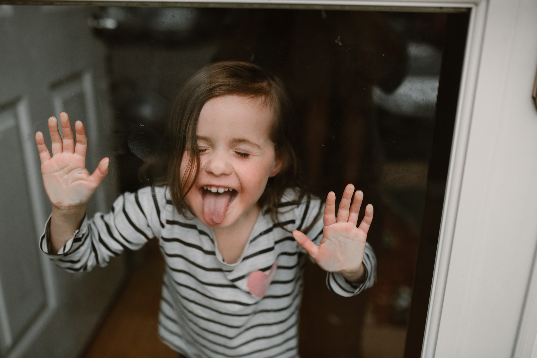 Girl in a striped shirt leans against a glass door and sticks her tongue out