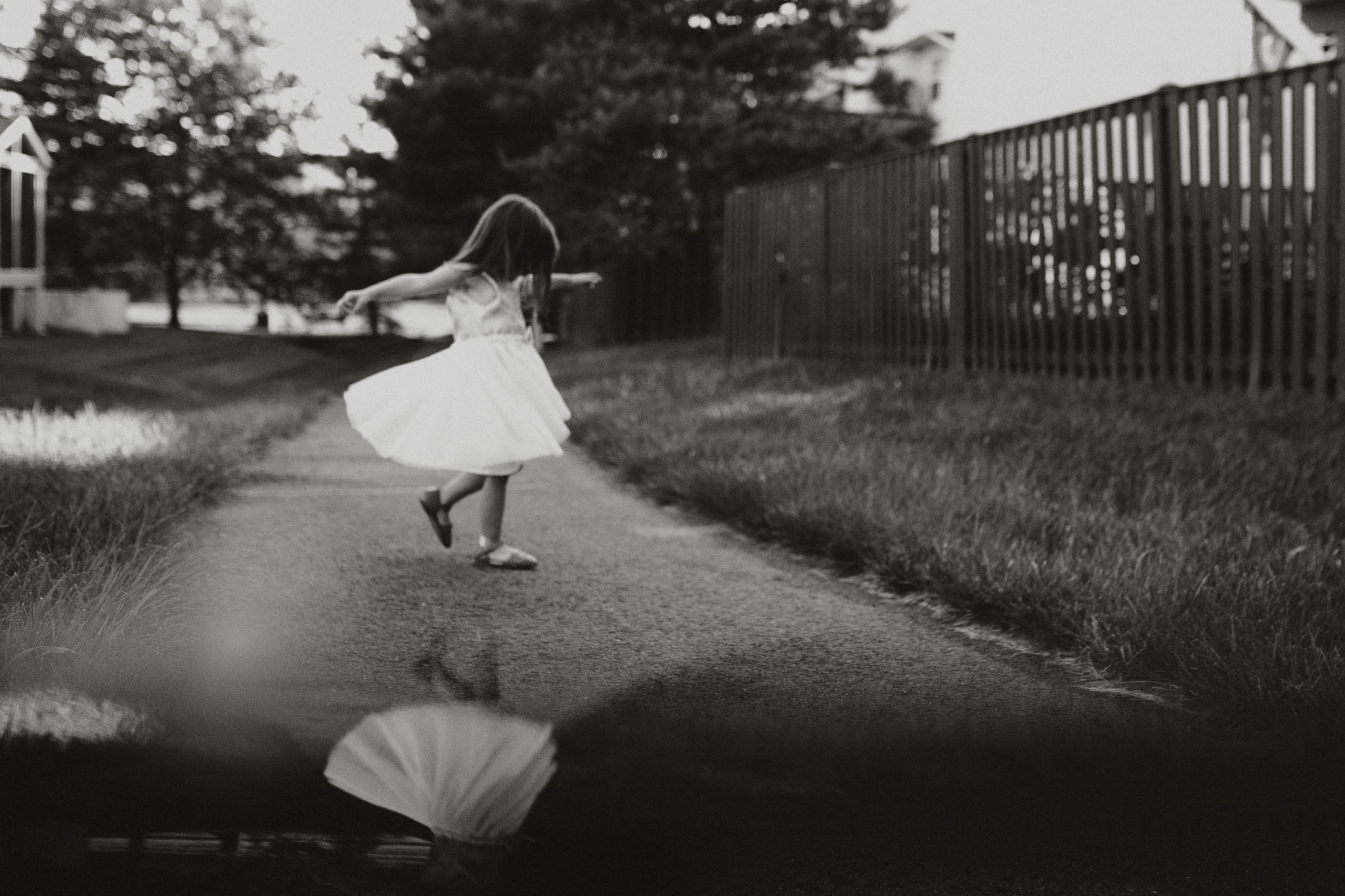 black and white image of a girl in a white dress twirling on a path with her reflection below her