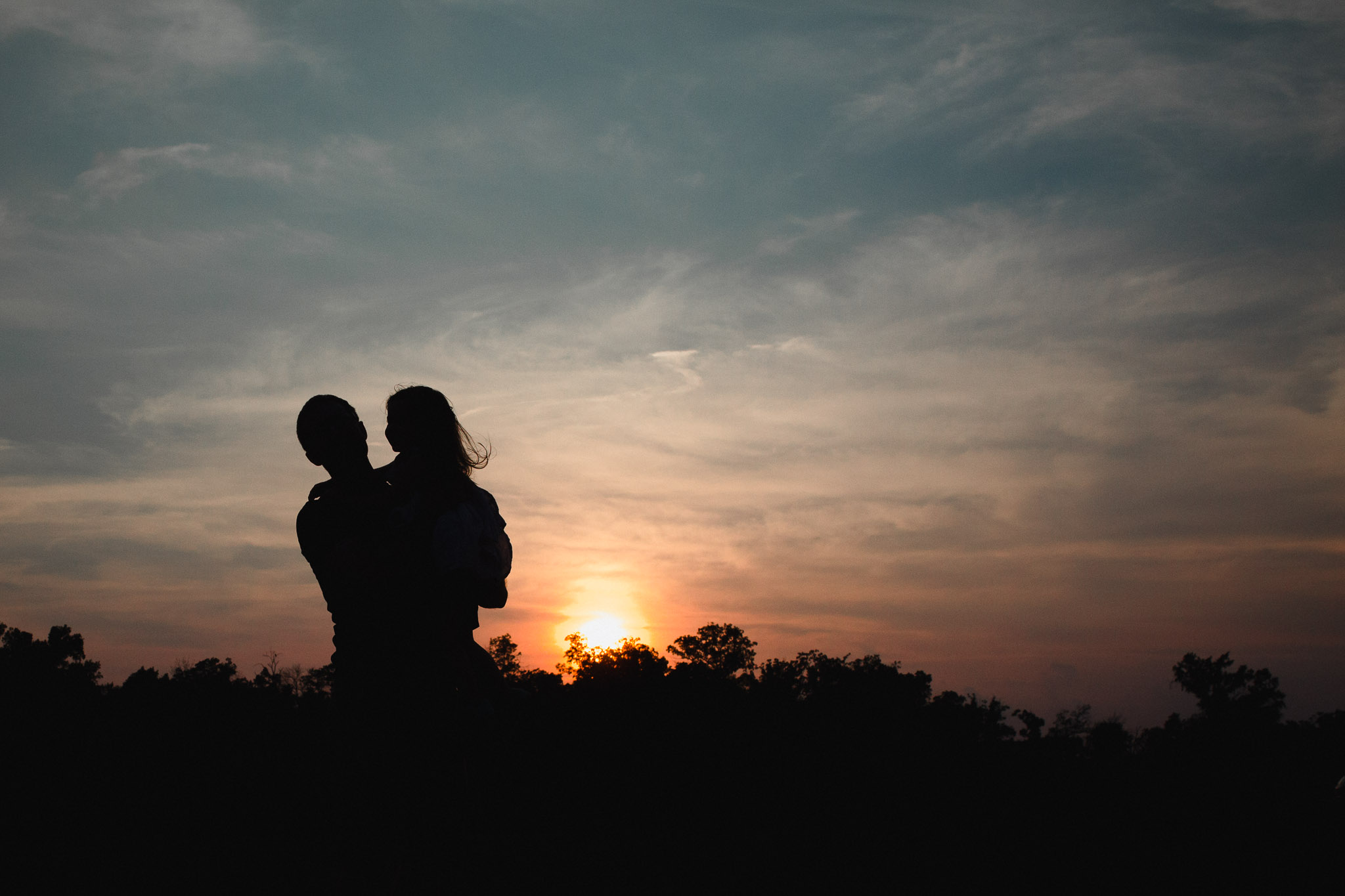 Silhouette of dad holding daughter at sunset