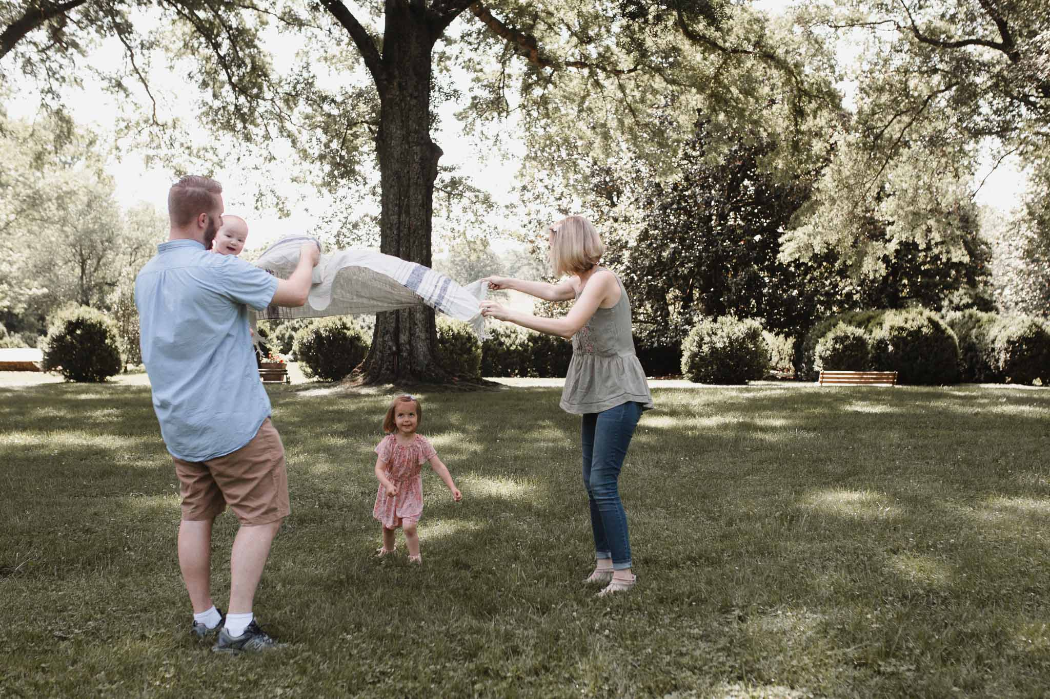 Parents hold out a blanket as their daughter runs under it at Morven Park in Leesburg, Virginia