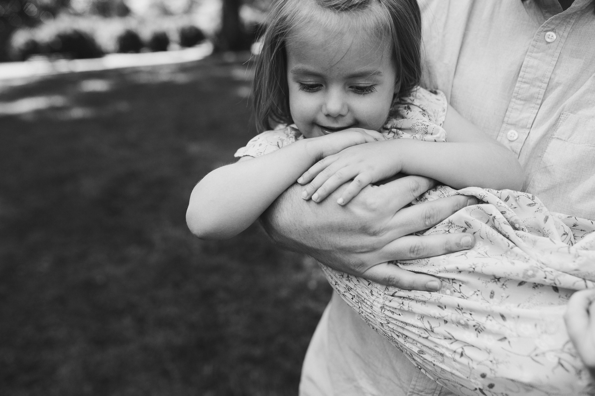 Black and white; toddler in her father's arms, her hands resting on his at Morven Park in Leesburg, Virginia