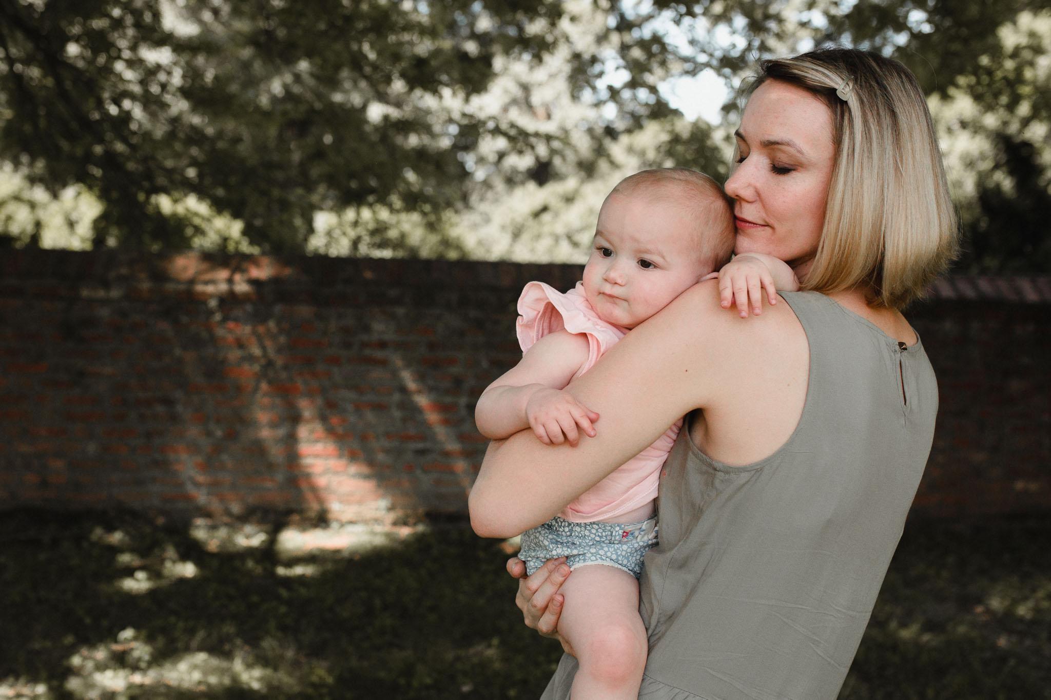 Mom closing her eyes holding her infant daughter at Morven Park in Leesburg, Virginia