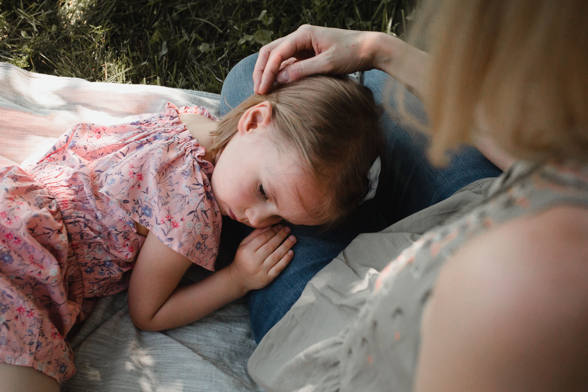 Toddler girl laying on her mother's lap as her mom strokes her hair at Morven Park in Leesburg, Virginia