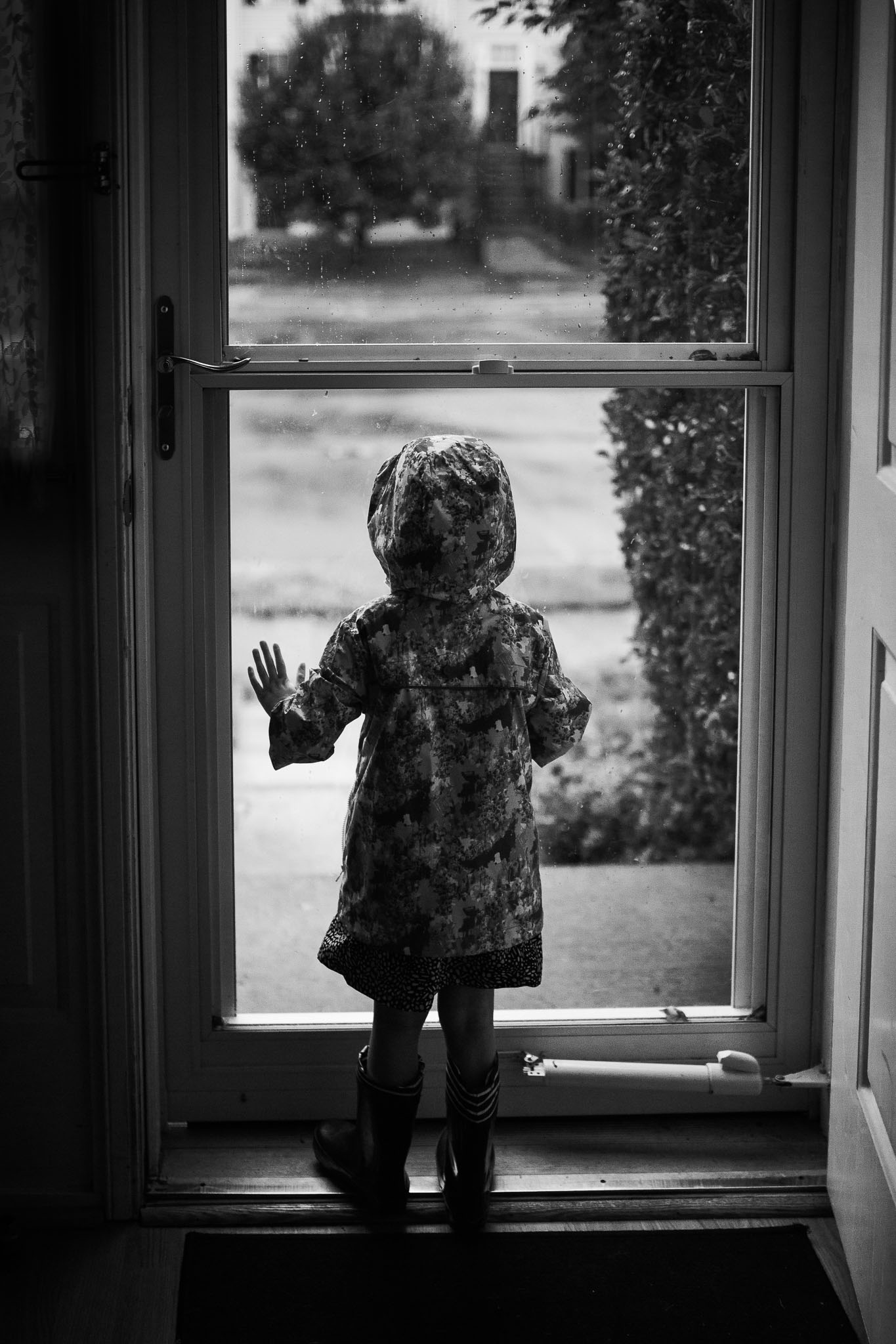 Black and white; girl in a raincoat and rain boots presses her hands and face against a glass door, preparing to go outside in the rain