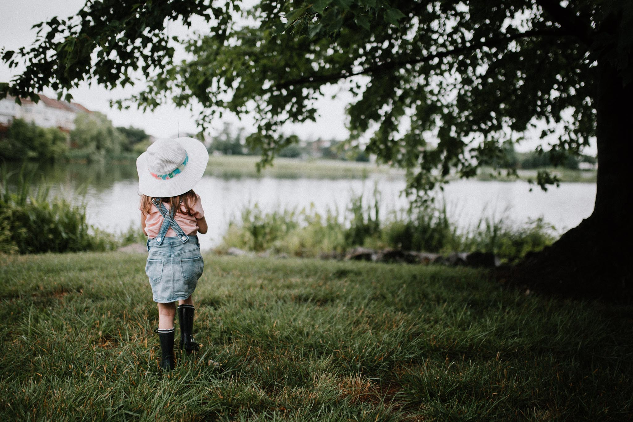 Girl in overalls and a white hat walks towards a lake, preparing to fish