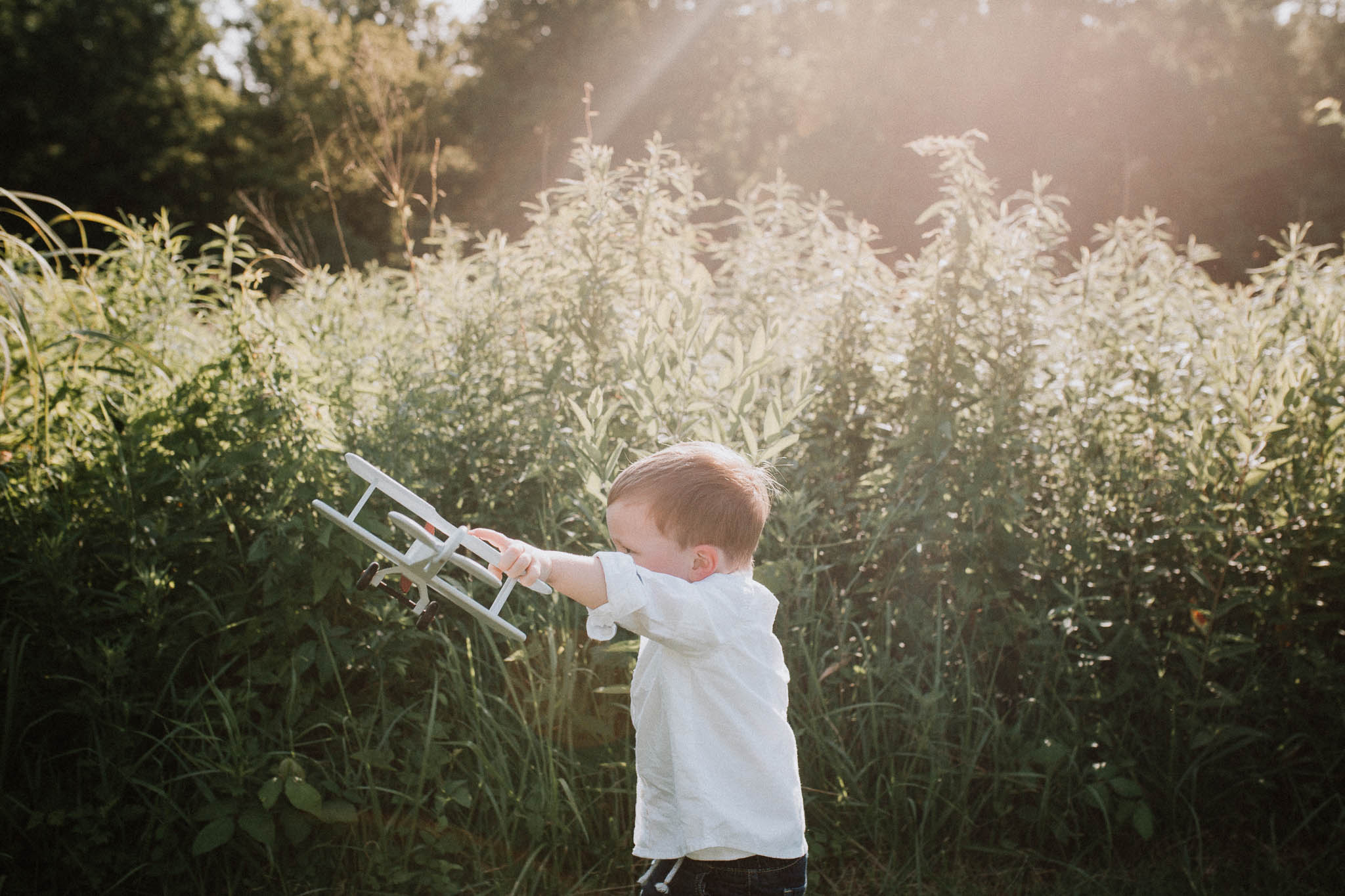 Toddler with a wooden airplane flies it through the air at Cabell's Mill in Chantilly, Virginia