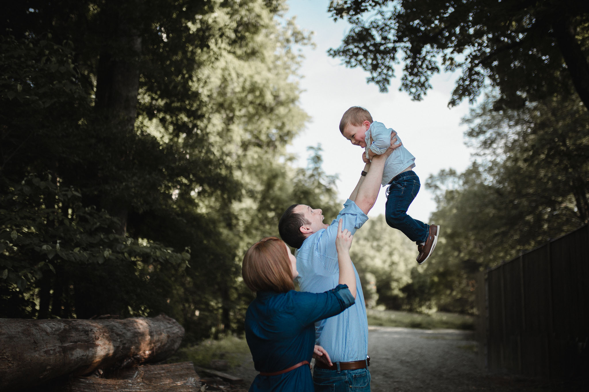 Dad lifts his son in the air while mom makes her son giggle at Cabell's Mill in Chantilly, Virginia