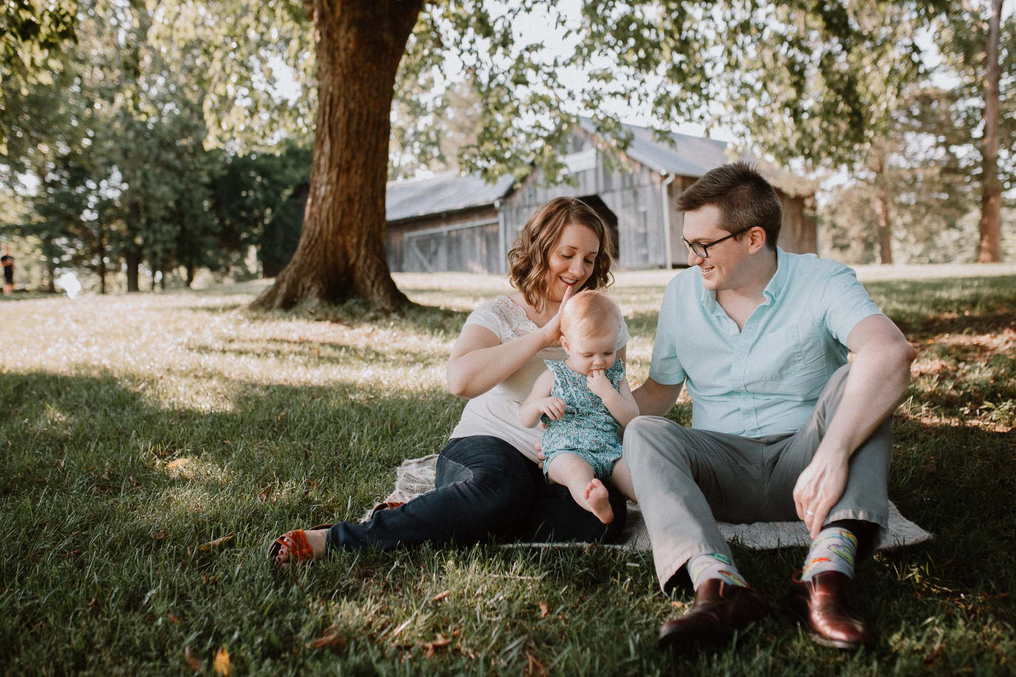 Family of three sits together on the grass at Claude Moore Park in Sterling, VA