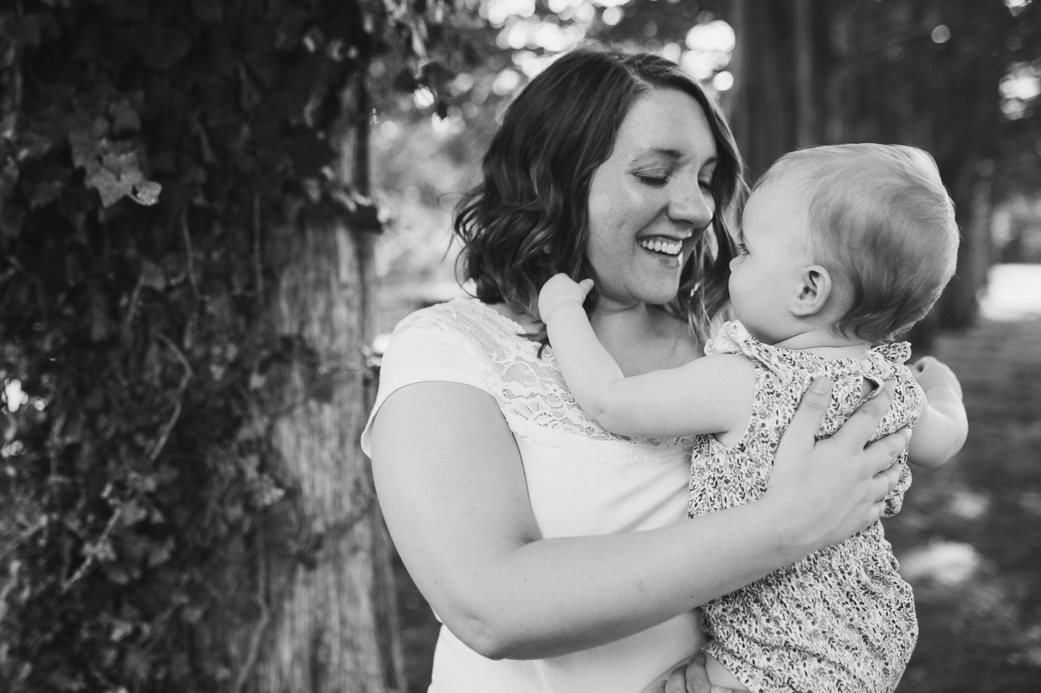 black and white; mom holding her daughter and laughing as she pulls her hair at Claude Moore Park in Sterling, VA