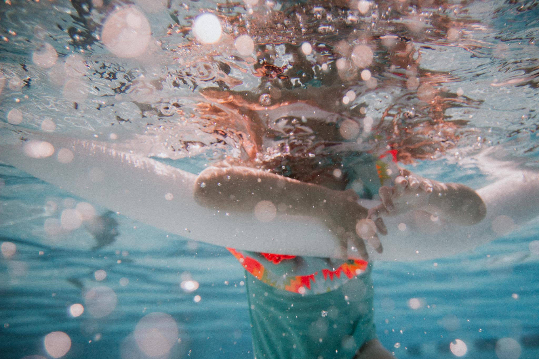 Underwater image of a girl holding onto a pool noodle in Ashburn, VA