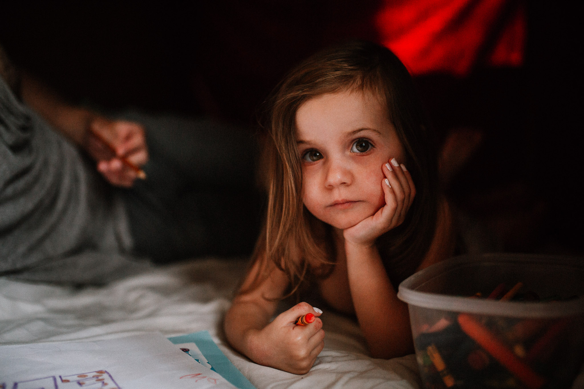 Portrait of a toddler laying in a blanket fort coloring