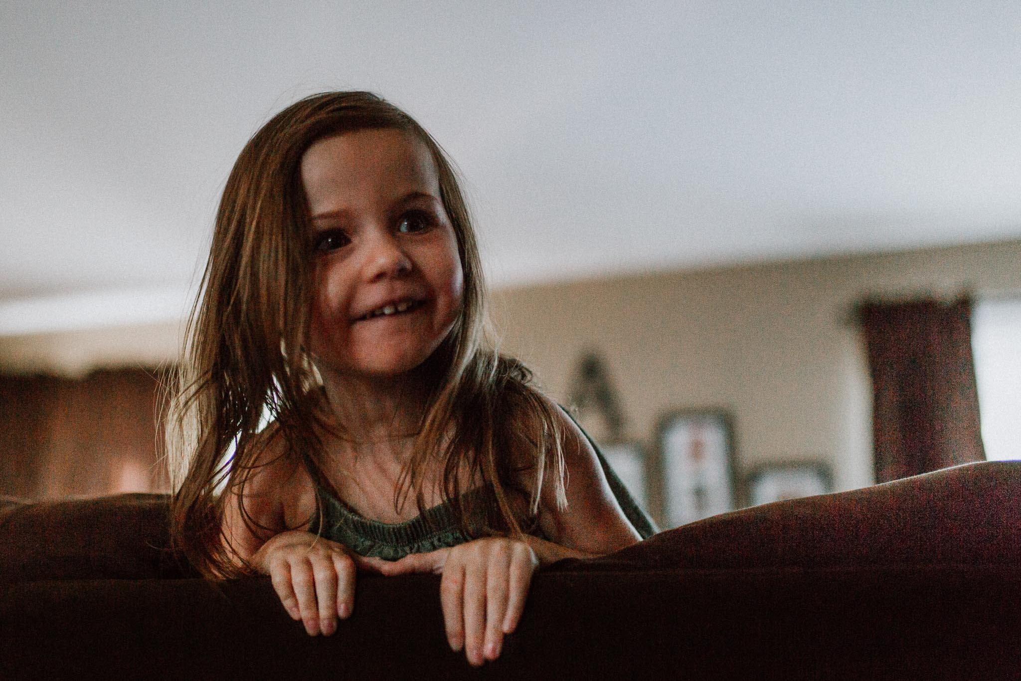 Young girl leaning over the back of a couch laughing