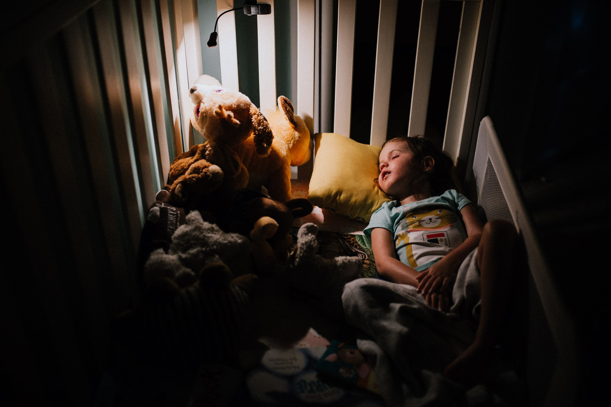 Young girl asleep in her bed next to a pile of stuffed animals and books