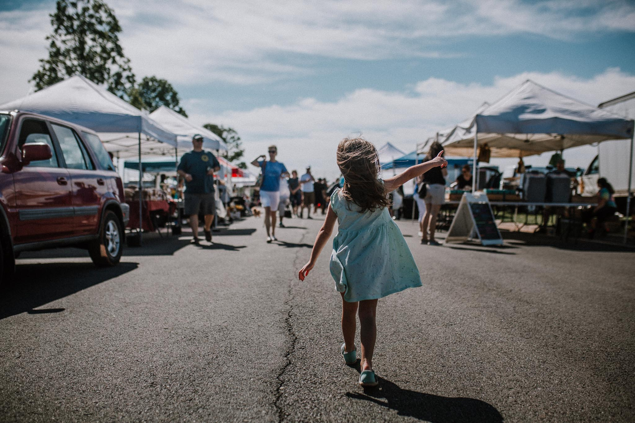 Toddler in a blue dress walking through a Farmer's Market pointing at something in the distance
