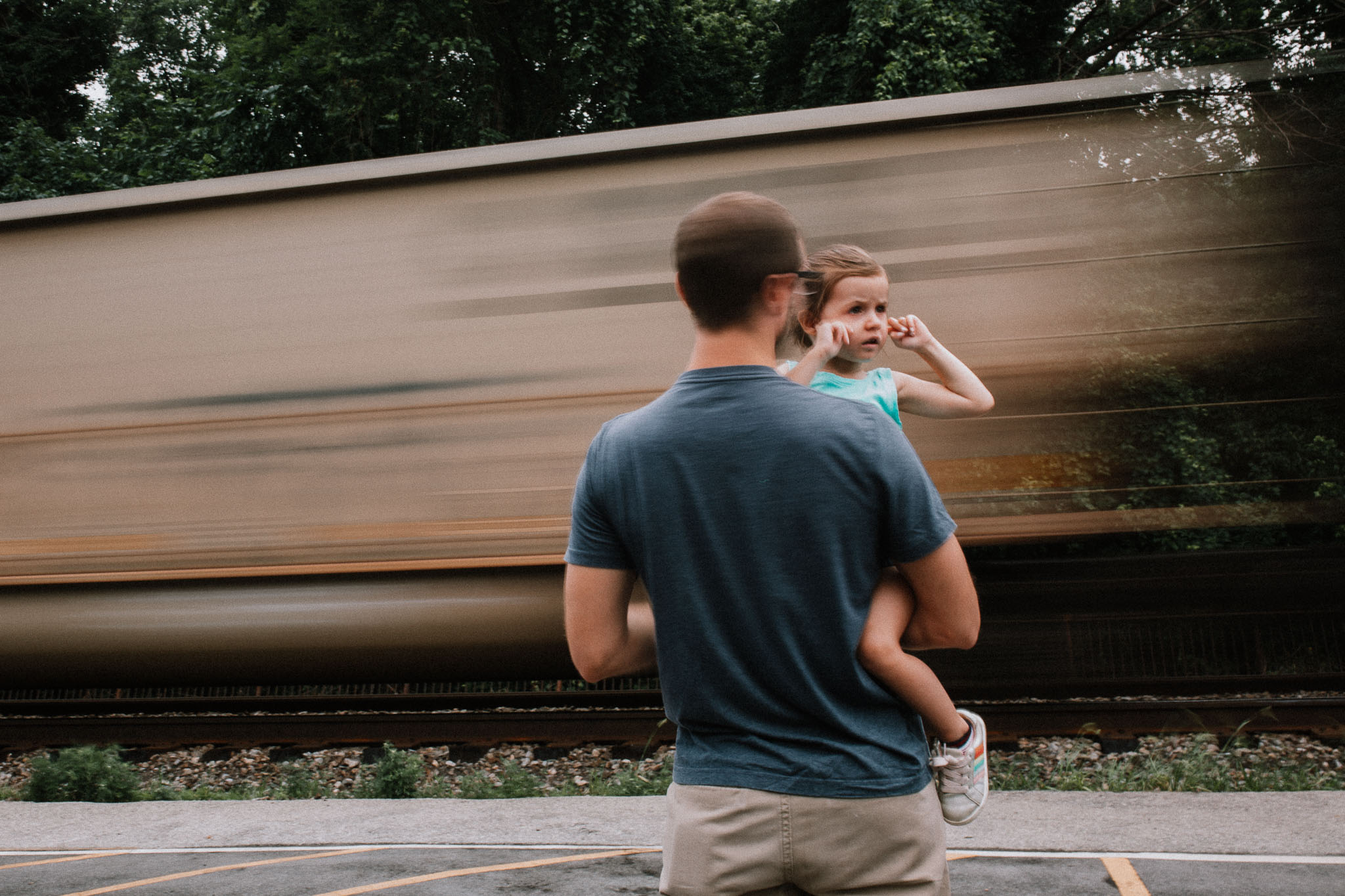Dad holding daughter who has her fingers in her ears as a train passes in the background in Harper's Ferry, WV