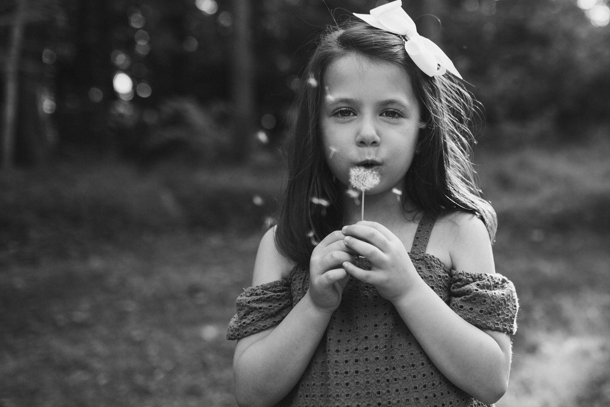 Black and white; girl blowing a dandelion