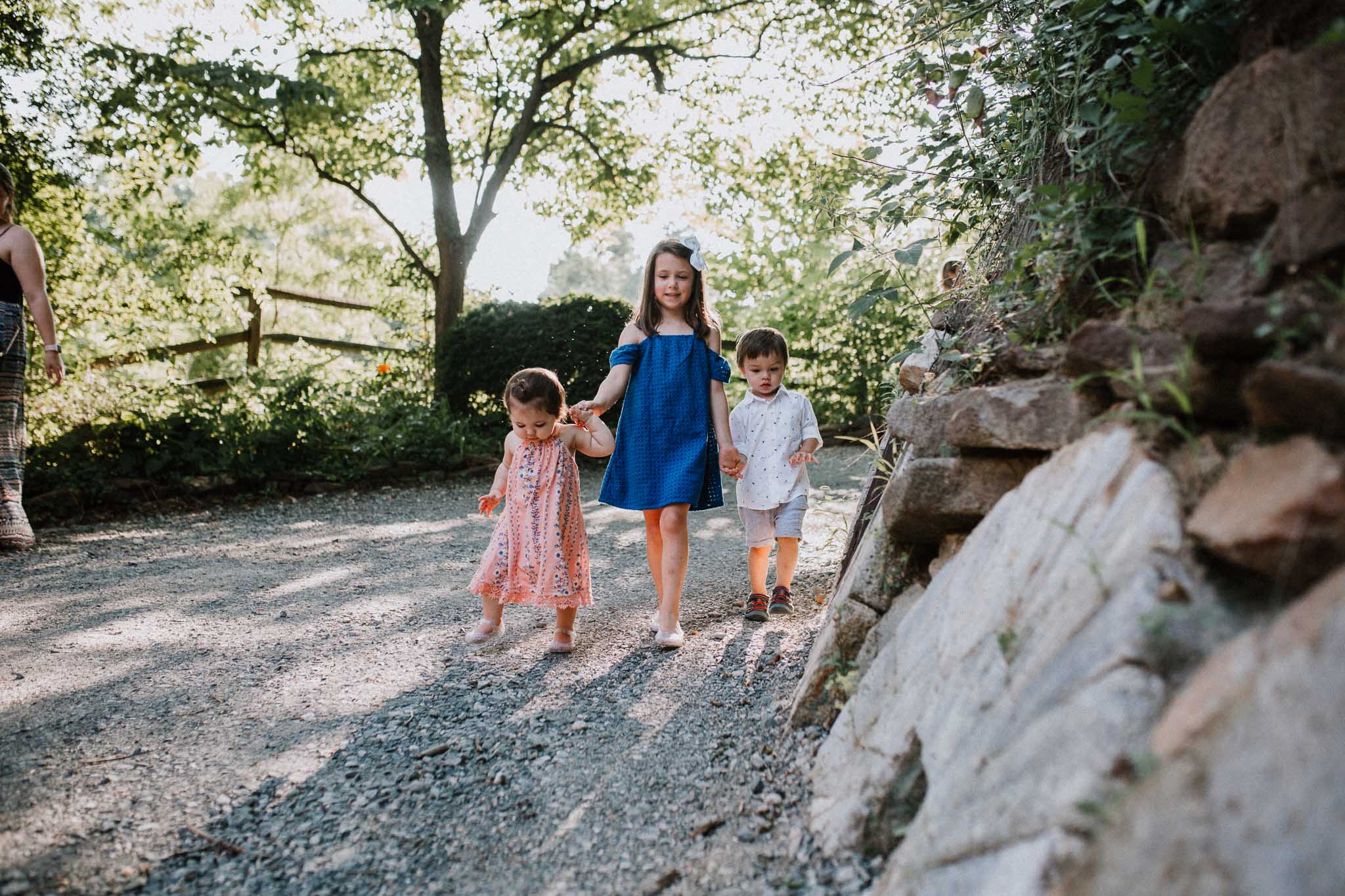three young kids holding hands and walking down a path at Colvin Run Mill in Great Falls
