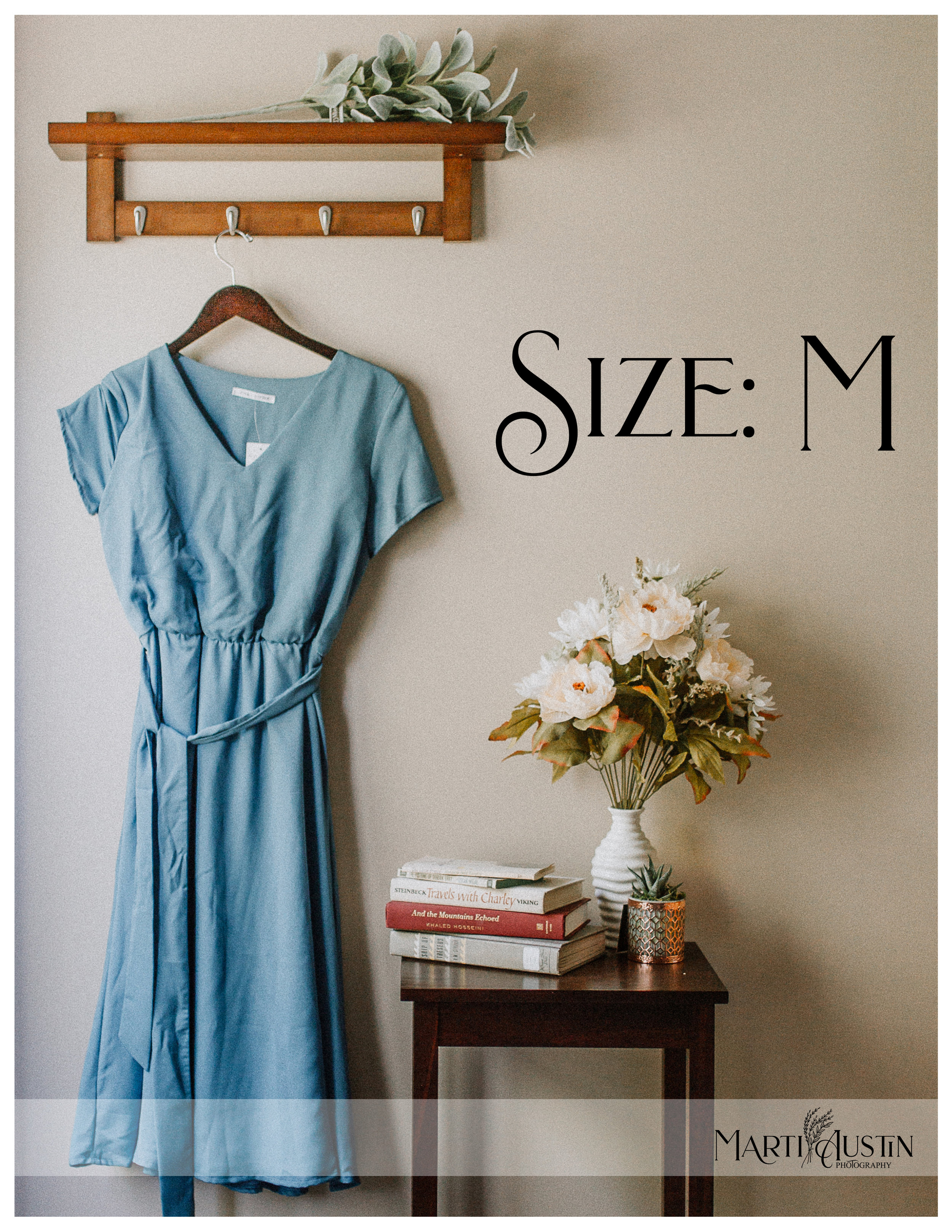 blue midi-dress hanging on the wall next to a table with books and flowers