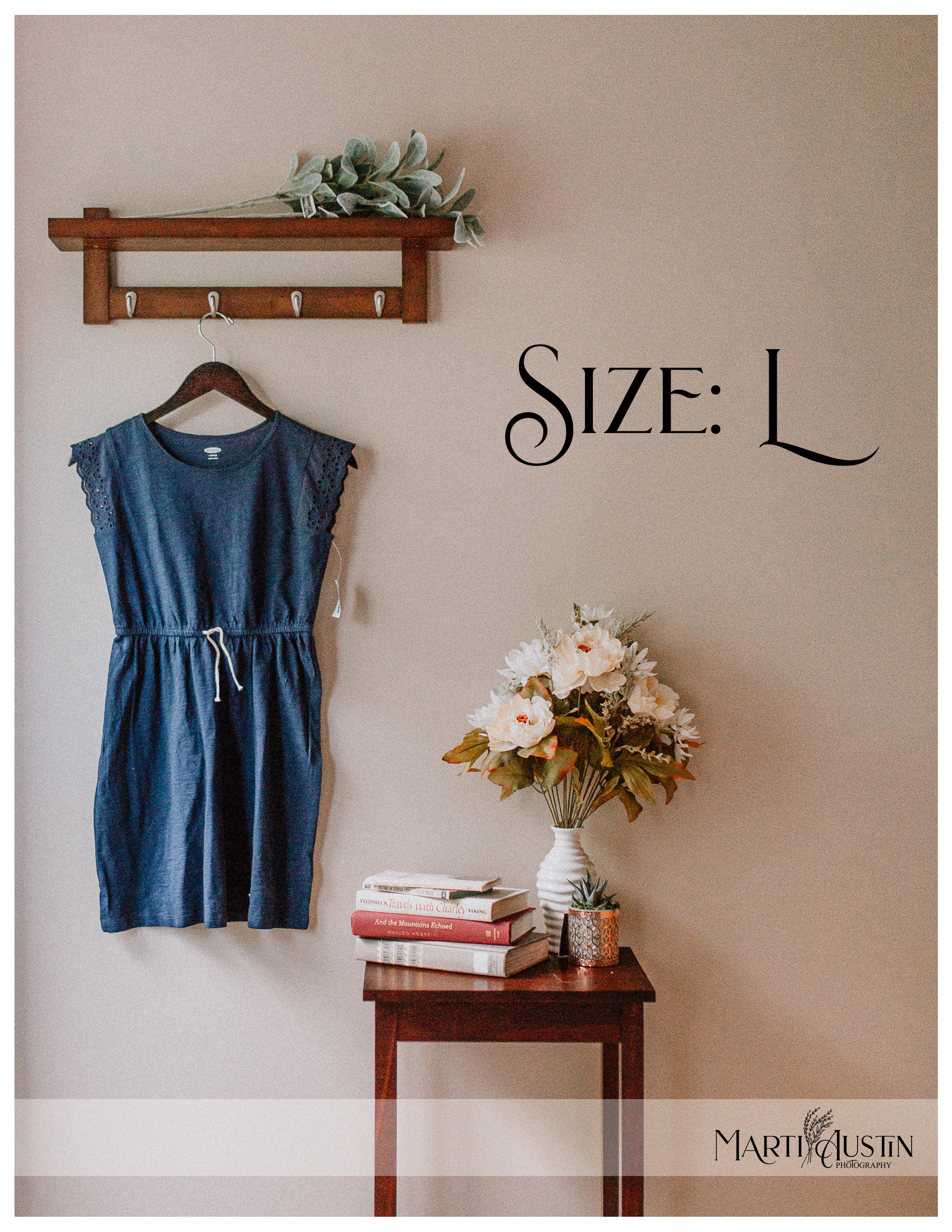 Girls blue dress hanging on the wall next to a table with books and flowers