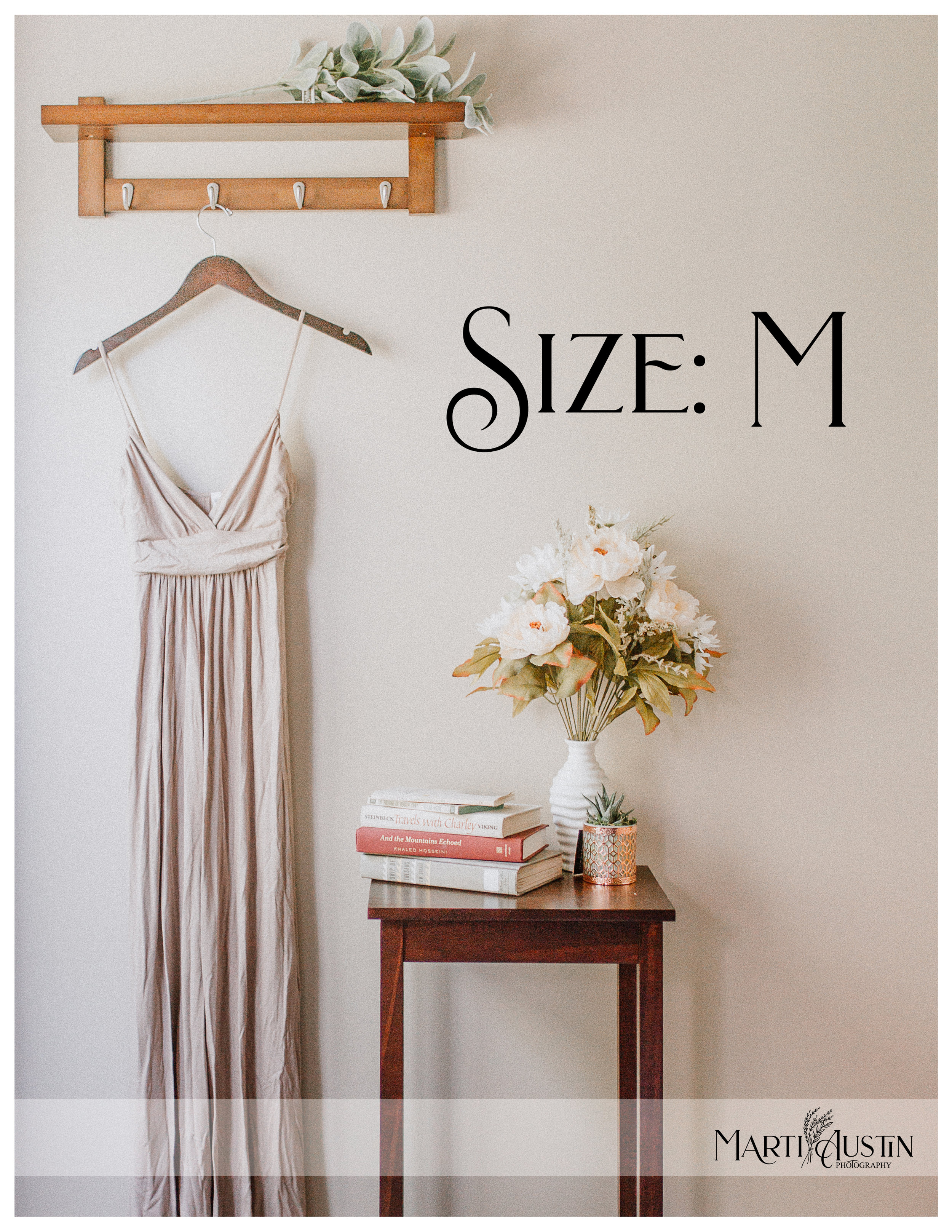 Long tan maternity dress hanging on the wall next to a table of books and flowwers