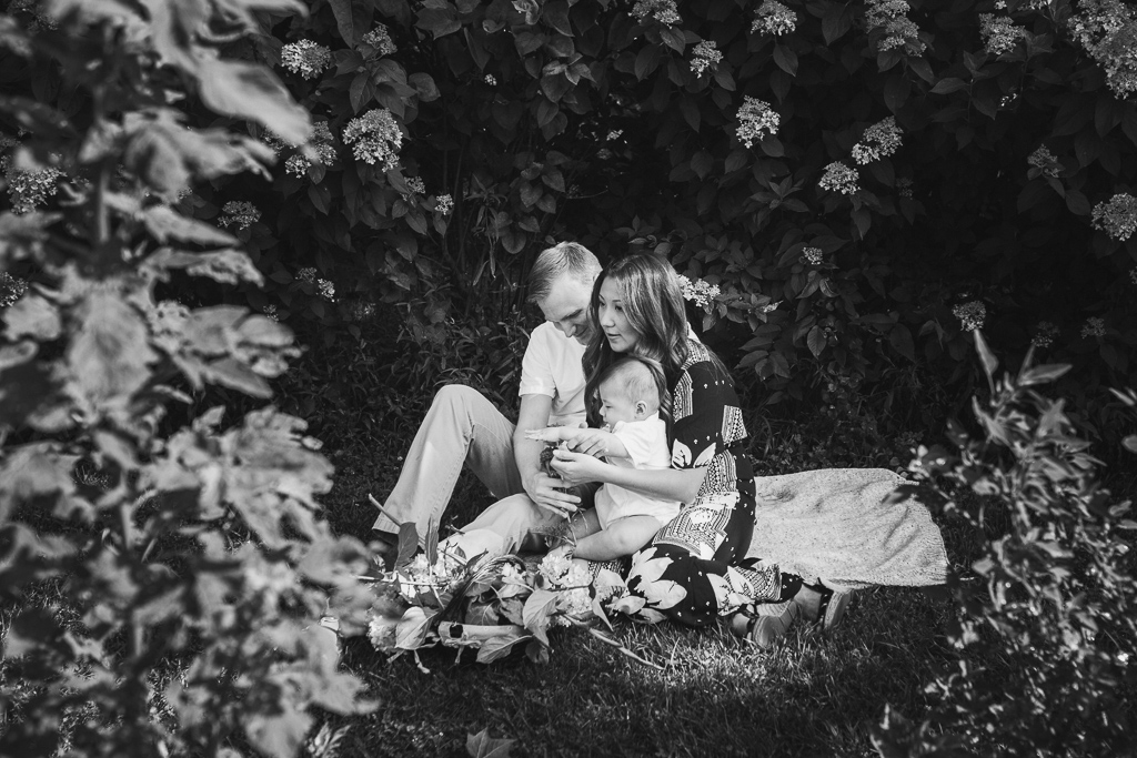 Black and white; family of three sitting together  at Fields of Flowers in Purcellville, VA
