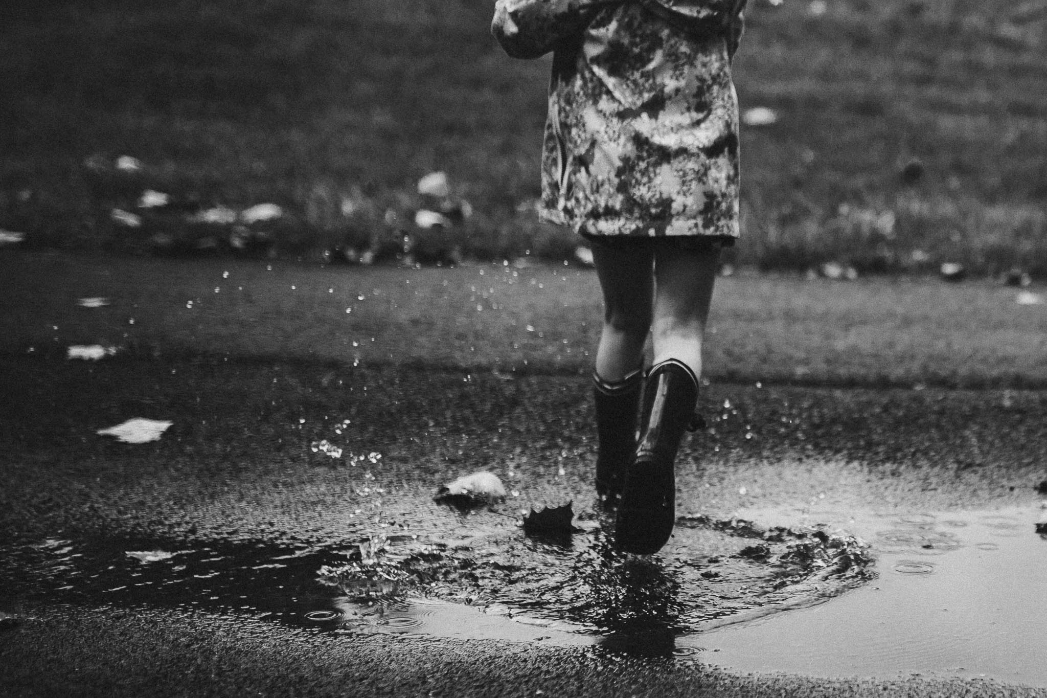 Black and white rainboots puddle jumping Toddler Girl Ashburn Virginia Lifestyle Documentary Family Marti Austin Photography