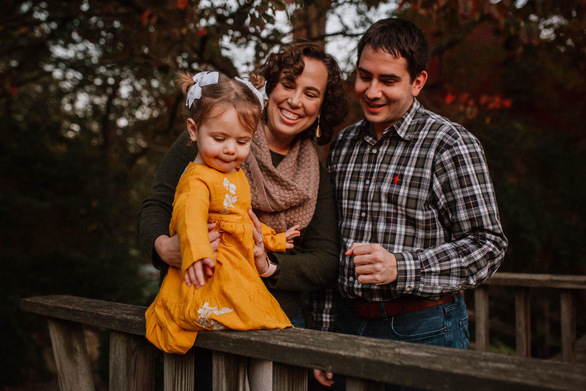 family of three toddler sitting on bridge fall sunset family lifestyle documentary Colvin Run Mill Great Falls Virginia Marti Austin Photography