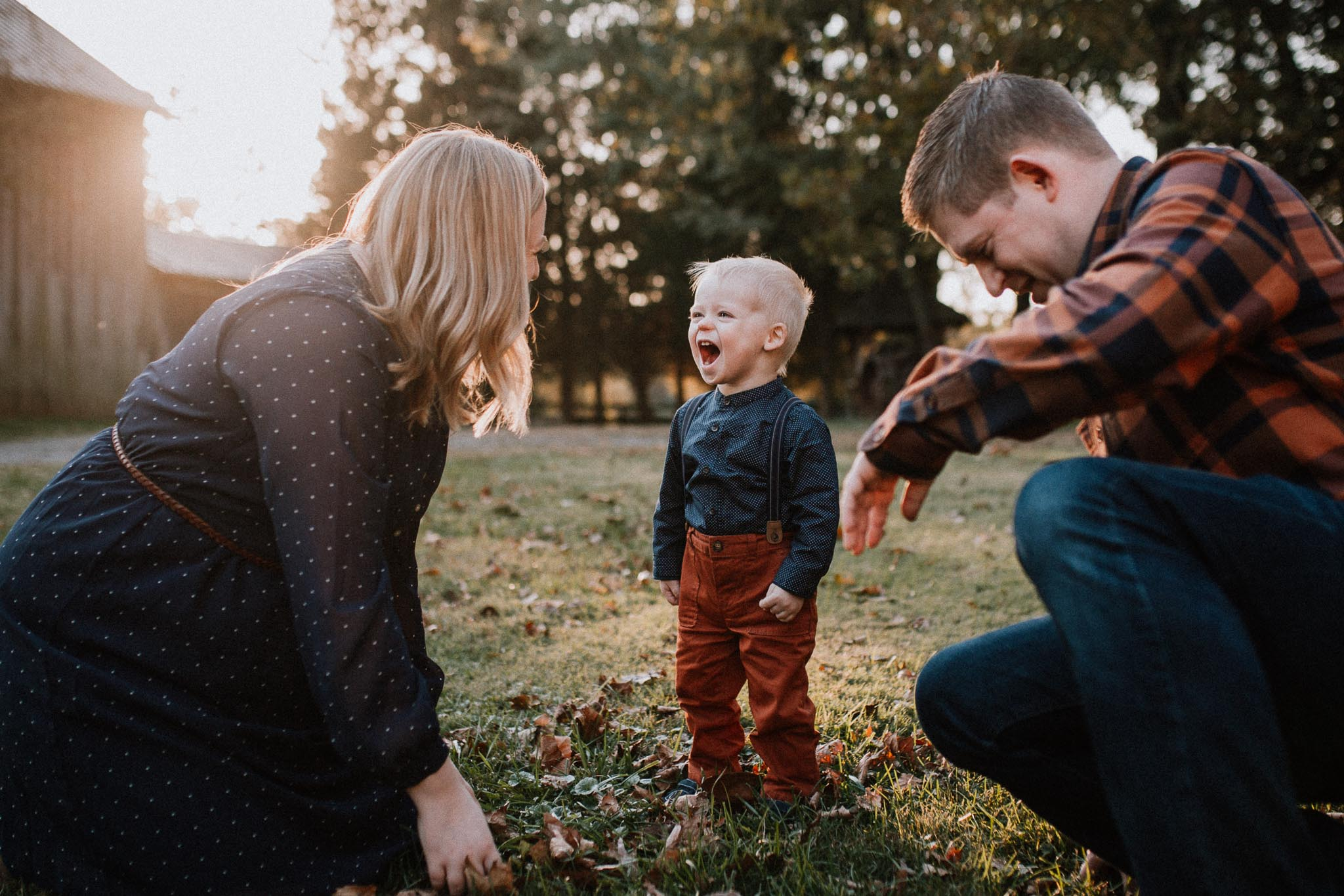 family of three play in leaves fall autumn lifestyle documentary Heritage Farm Museum Sterling Loudoun Virginia Family Marti Austin Photography