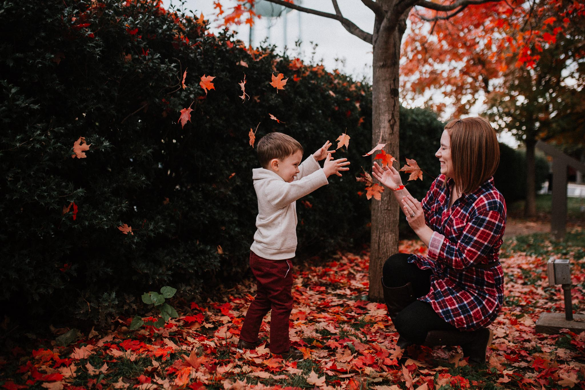 mother son playing in leaves fall autumn lifestyle documentary family Historic Old Town Manassas Virginia Marti Austin Photography
