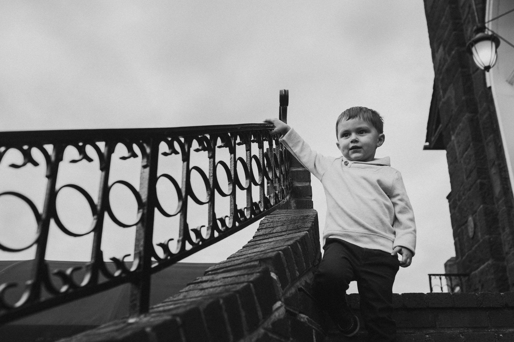 black and white toddler boy portrait stairs fall autumn lifestyle documentary family Historic Old Town Manassas Virginia Marti Austin Photography