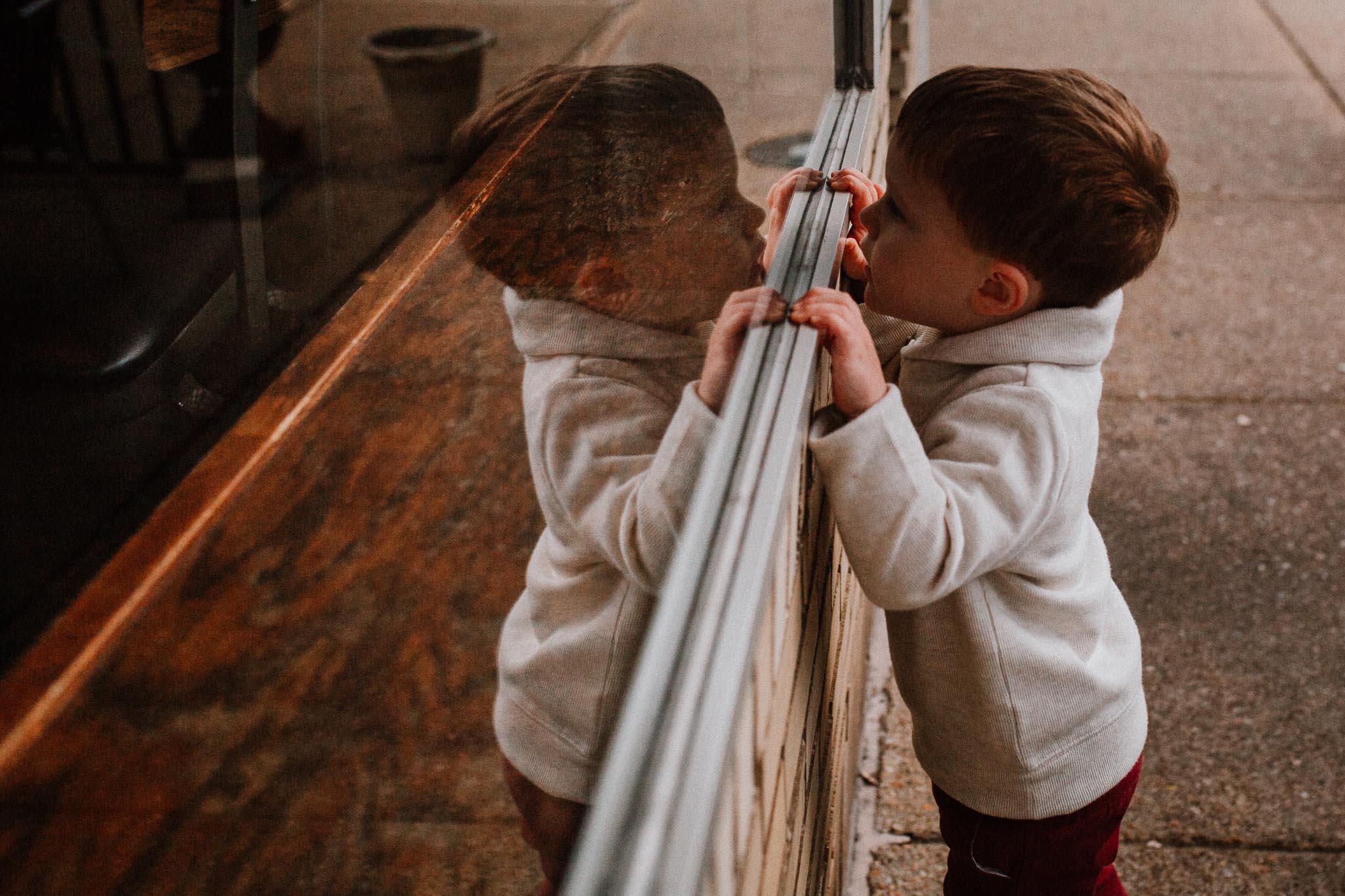toddler boy window reflection fall autumn lifestyle documentary family Historic Old Town Manassas Virginia Marti Austin Photography