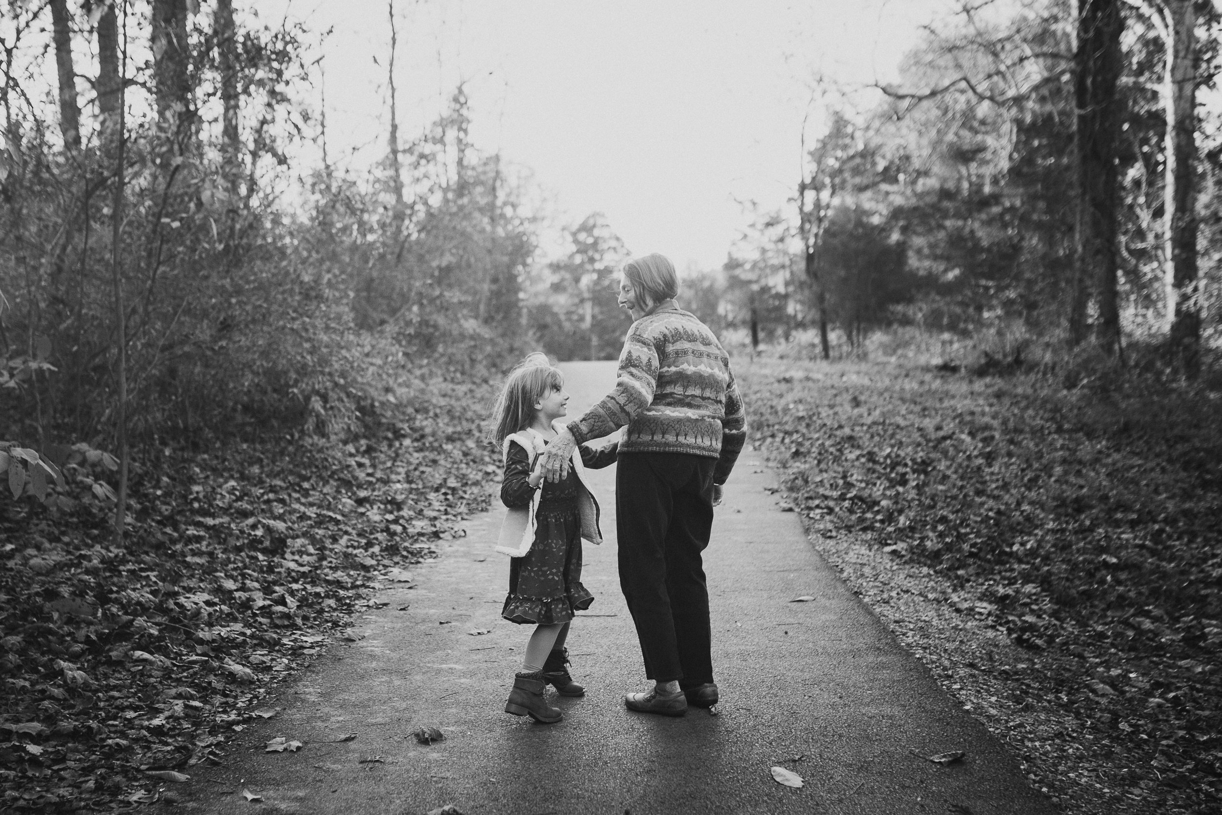 black and white grandmother granddaughter walk forest path hold hands lifestyle family documentary fall autumn sunset golden Cabell's Mill Ellanor C Lawrence Chantilly Virginia Marti Austin Photography